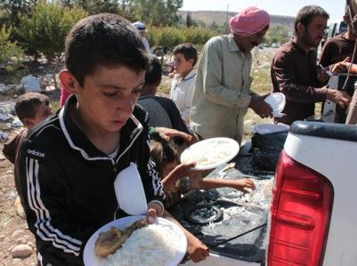 Niño yezidí recibiendo ración de comida